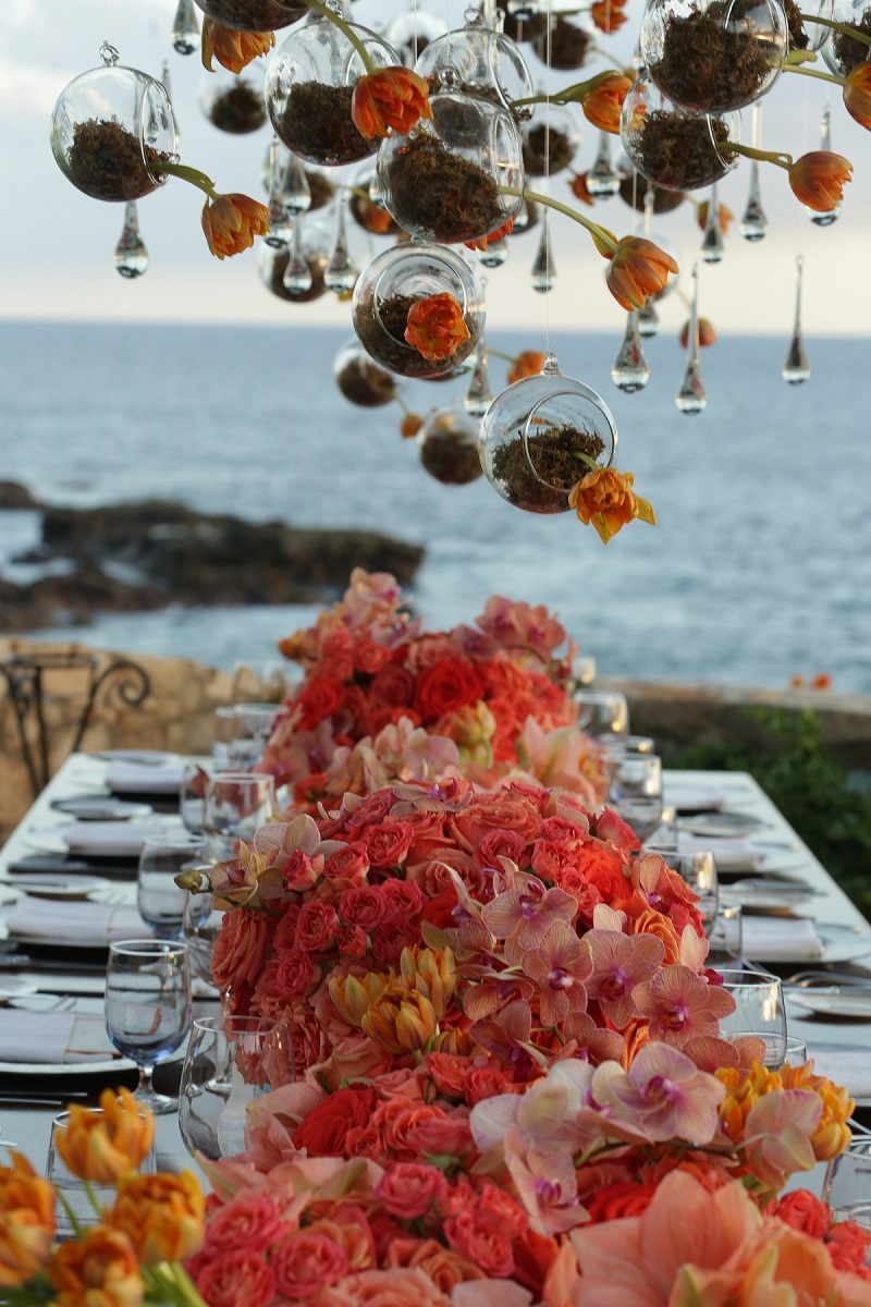 hanging flowers over wedding tables with orange and coral flowers elena damy event design 800jpg