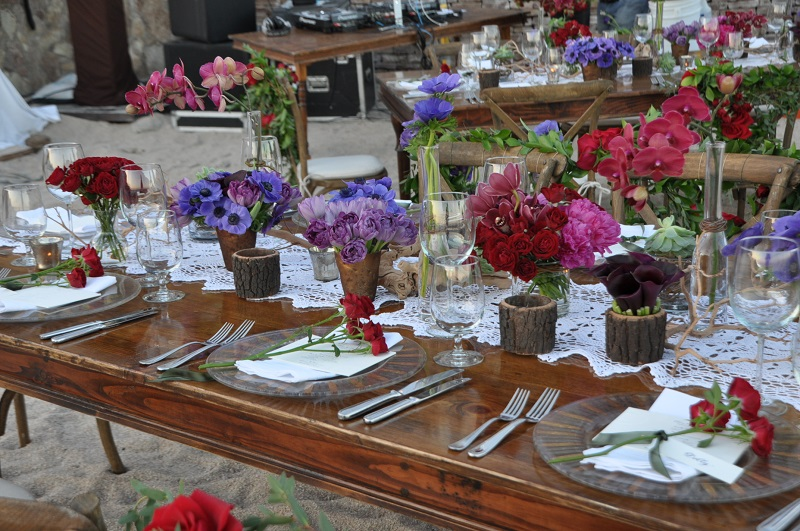 red and purple flowers beach weddings mexico elena damy floral design los cabos wooden tables lace linens 1