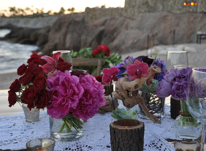 red and purple flowers beach weddings mexico elena damy floral design los cabos wooden tables lace linens 5