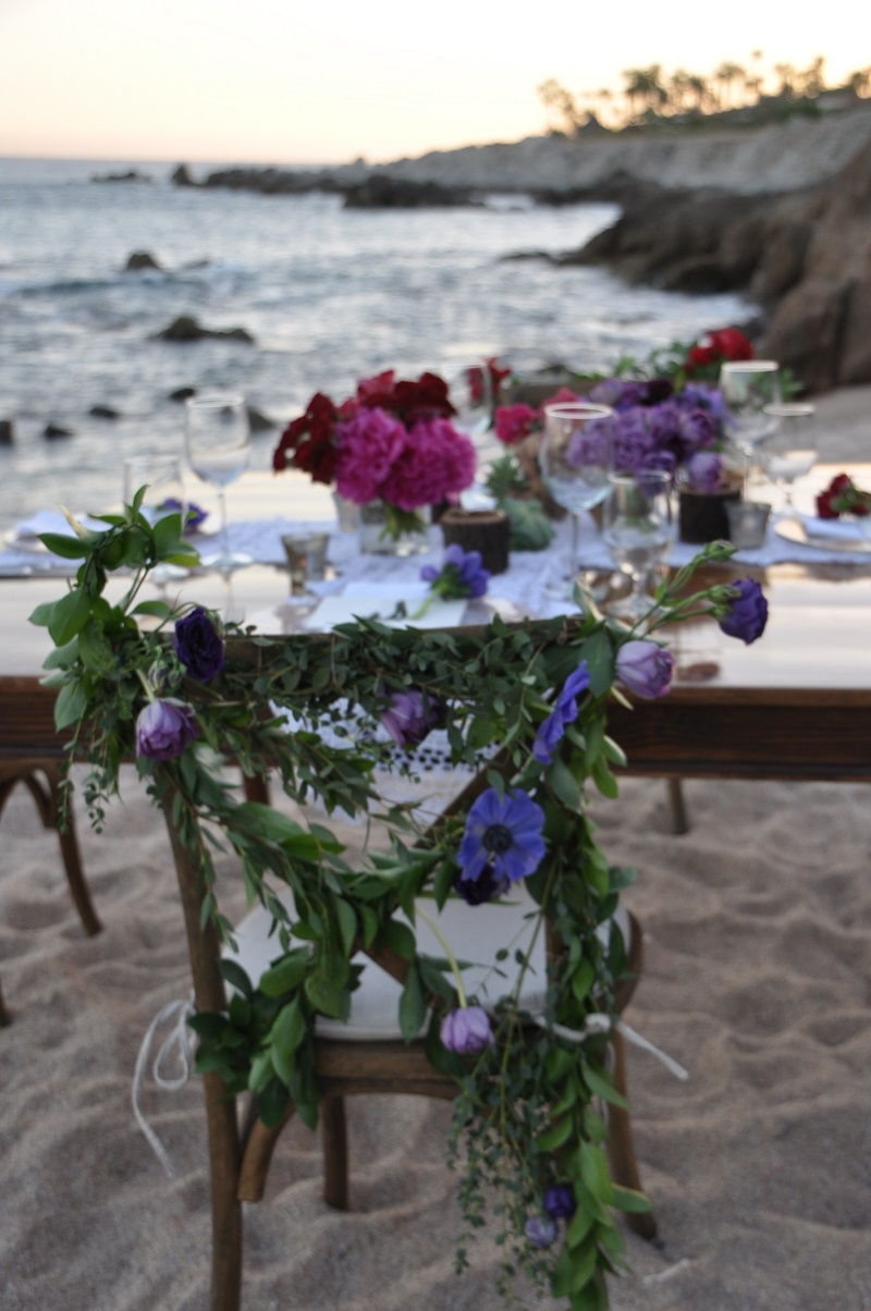 red and purple flowers beach weddings mexico elena damy floral design los cabos wooden tables lace linens purple anemones