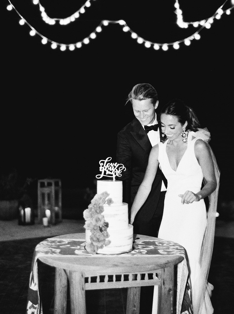 black-and-white-photo-of-bride-and-groom-cutting-the-cake-los-cabos-destination-weddings-elena-damy-destination-wedding-planners