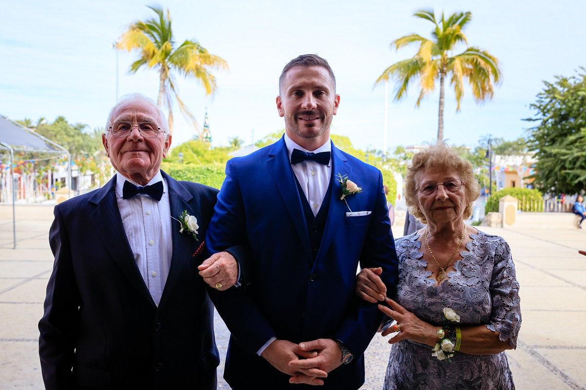 groom walks down aisle with parents church wedding